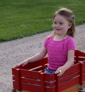 Little_girl_in_red_wagon_by_eyenoticed